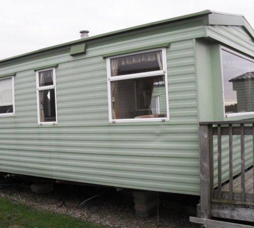 green caravan with decking